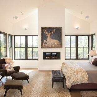 サンフランシスコの広いトランジショナルスタイルのおしゃれな主寝室 (淡色無垢フローリング、横長型暖炉、白い壁、漆喰の暖炉まわり、ベージュの床) のレイアウト