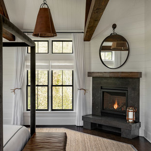 Large farmhouse master dark wood floor and brown floor bedroom photo in New York with white walls, a corner fireplace and a stone fireplace