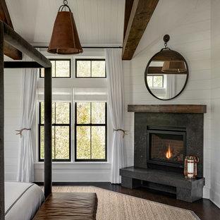 ニューヨークの広いカントリー風おしゃれな主寝室 (白い壁、濃色無垢フローリング、コーナー設置型暖炉、石材の暖炉まわり、茶色い床)