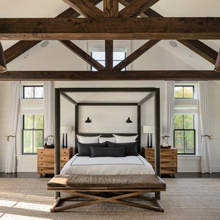 This is an example of a large country master bedroom in New York with white walls, dark hardwood floors and brown floor.