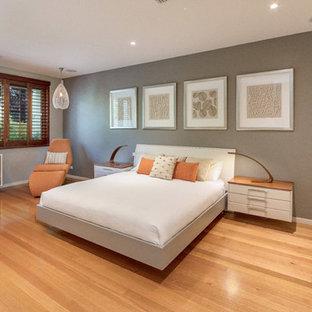 Contemporary bedroom in Canberra - Queanbeyan with grey walls, medium hardwood floors and brown floor.
