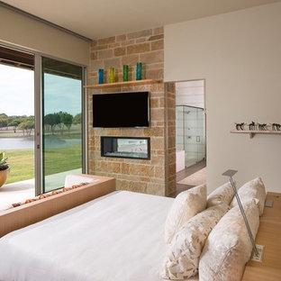 Modelo de habitación de invitados vintage, de tamaño medio, con paredes beige, suelo de baldosas de porcelana, chimenea de doble cara y marco de chimenea de piedra