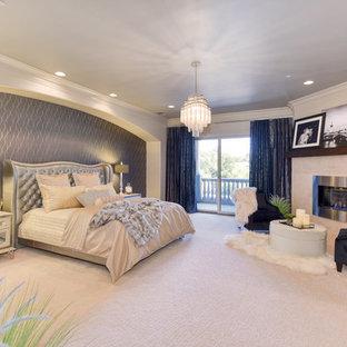 Esempio di una grande camera matrimoniale moderna con pareti beige, moquette, camino ad angolo, cornice del camino in pietra e pavimento beige