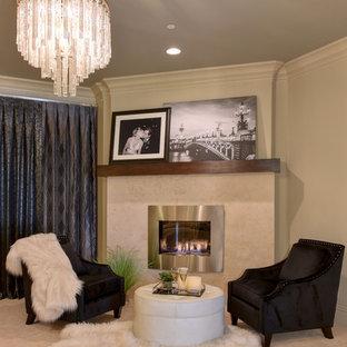 Ispirazione per una grande camera matrimoniale minimalista con pareti beige, moquette, camino ad angolo, cornice del camino in pietra e pavimento beige