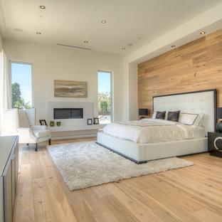 На фото: большая хозяйская спальня в современном стиле с бежевым полом, белыми стенами, светлым паркетным полом, горизонтальным камином и фасадом камина из плитки