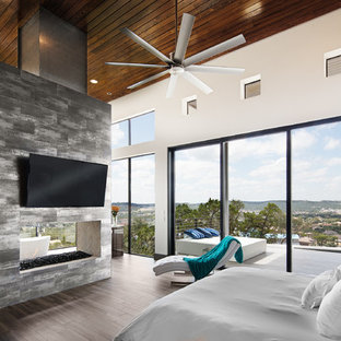 Photo of a large modern master bedroom in Austin with white walls, ceramic floors, a two-sided fireplace, a metal fireplace surround and brown floor.