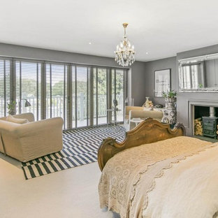 Inspiration for a mid-sized transitional bedroom in London with grey walls, carpet, a wood stove and beige floor.