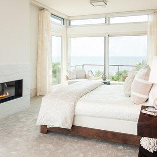ボストンの大きいコンテンポラリースタイルのおしゃれな主寝室 (白い壁、横長型暖炉、竹フローリング、ベージュの床、石材の暖炉まわり) のレイアウト