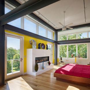 Foto di una grande camera matrimoniale design con pareti gialle, parquet chiaro, camino lineare Ribbon e cornice del camino in intonaco