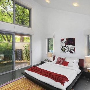 Ejemplo de dormitorio principal, contemporáneo, pequeño, sin chimenea, con paredes blancas, suelo negro y suelo de baldosas de porcelana