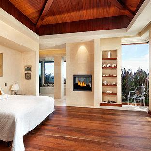 Foto di una camera matrimoniale tropicale con pareti beige, parquet scuro e camino bifacciale