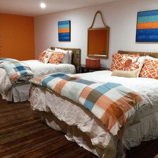 Imagen de habitación de invitados moderna, grande, sin chimenea, con parades naranjas y suelo de travertino