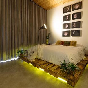 Bedroom - huge industrial master concrete floor bedroom idea in Austin with white walls