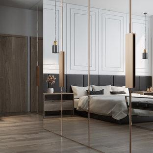 Mittelgroßes Modernes Schlafzimmer im Loft-Style mit weißer Wandfarbe, braunem Holzboden und buntem Boden in Los Angeles