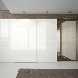 Foto di una grande camera matrimoniale moderna con pareti grigie e pavimento in cemento