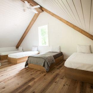 Imagen de dormitorio tipo loft, minimalista, de tamaño medio, con paredes blancas, suelo vinílico y suelo marrón