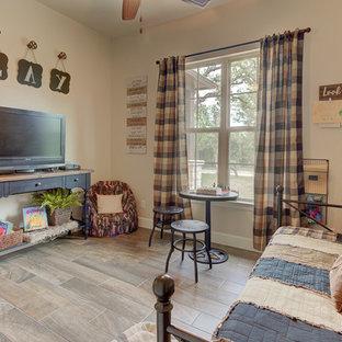 Immagine di una camera degli ospiti rustica di medie dimensioni con pareti beige, pavimento in gres porcellanato, camino classico, cornice del camino in pietra e pavimento marrone