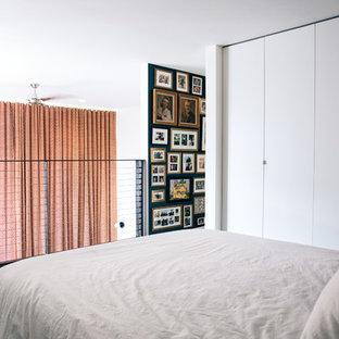 Diseño de dormitorio tipo loft, actual, pequeño, con paredes blancas, moqueta y suelo gris