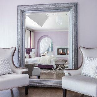 Imagen de dormitorio principal, moderno, grande, con paredes púrpuras, suelo de madera en tonos medios, chimenea de doble cara y marco de chimenea de baldosas y/o azulejos