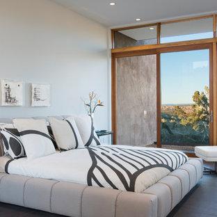Modelo de dormitorio principal, minimalista, de tamaño medio, sin chimenea, con paredes blancas, suelo de baldosas de porcelana y suelo gris
