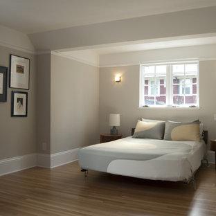 Immagine di una camera matrimoniale minimal di medie dimensioni con pavimento in legno massello medio e pareti grigie