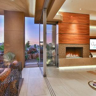 Großes Modernes Hauptschlafzimmer mit beiger Wandfarbe, Porzellan-Bodenfliesen, Kamin, gefliester Kaminumrandung und beigem Boden in Los Angeles