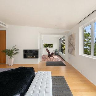 シアトルの巨大なビーチスタイルのおしゃれな主寝室 (白い壁、コーナー設置型暖炉、漆喰の暖炉まわり、無垢フローリング、茶色い床)