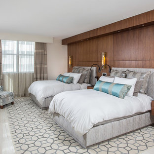Large contemporary guest bedroom in Miami with beige walls, limestone floors and no fireplace.