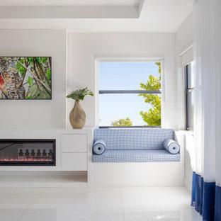 Bild på ett stort funkis huvudsovrum, med vita väggar, marmorgolv, en hängande öppen spis, en spiselkrans i trä och vitt golv