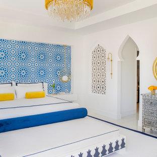 Imagen de dormitorio principal, minimalista, grande, con paredes blancas, suelo de mármol, chimeneas suspendidas, marco de chimenea de madera y suelo blanco