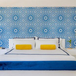 マイアミの広いモダンスタイルのおしゃれな主寝室 (白い壁、大理石の床、吊り下げ式暖炉、木材の暖炉まわり、白い床)