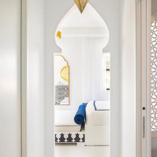 Immagine di una grande camera matrimoniale minimalista con pareti bianche, pavimento in marmo, camino sospeso, cornice del camino in legno e pavimento bianco