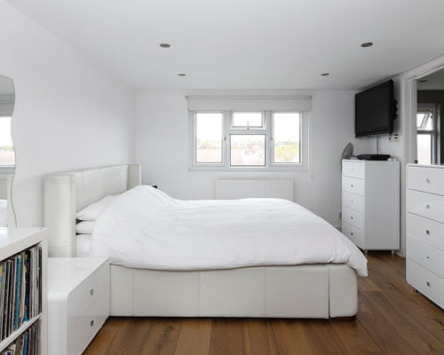 Mid-sized contemporary guest medium tone wood floor bedroom idea in London  with white walls