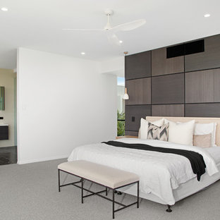 Photo of a beach style master bedroom in Gold Coast - Tweed with white walls, carpet and grey floor.
