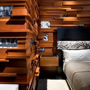 На фото: большая гостевая спальня в современном стиле с коричневыми стенами, полом из сланца, двусторонним камином, фасадом камина из камня и черным полом