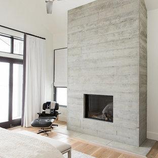 На фото: хозяйские спальни в стиле современная классика с белыми стенами, светлым паркетным полом, стандартным камином и фасадом камина из бетона