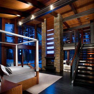 Imagen de dormitorio principal, actual, grande, con paredes marrones, suelo de madera oscura, chimenea de doble cara, marco de chimenea de piedra y suelo negro