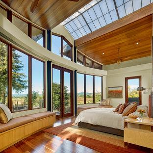 Modelo de dormitorio principal, minimalista, de tamaño medio, con paredes beige, suelo de madera en tonos medios y chimenea de esquina