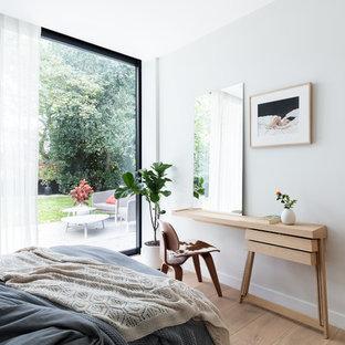 Imagen de habitación de invitados clásica renovada, de tamaño medio, con suelo de madera clara y paredes blancas