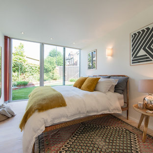 Photo of a contemporary bedroom in London with white walls and beige floors.