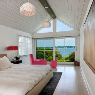 Mid-sized coastal master light wood floor and beige floor bedroom photo in New York with white walls