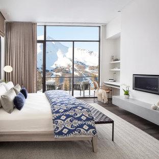 Inspiration för moderna sovrum, med vita väggar, mörkt trägolv, en bred öppen spis, en spiselkrans i metall och brunt golv