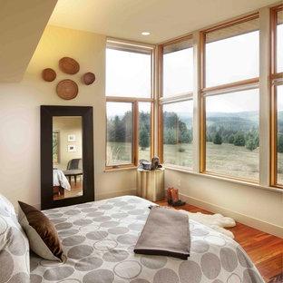 Bedroom - large contemporary master medium tone wood floor bedroom idea in Portland with beige walls