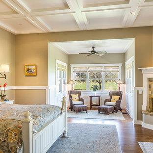 На фото: большая спальня в стиле кантри с бежевыми стенами, паркетным полом среднего тона, угловым камином и фасадом камина из плитки с