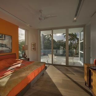 Modelo de dormitorio tipo loft, minimalista, grande, con parades naranjas, suelo de madera clara y suelo marrón