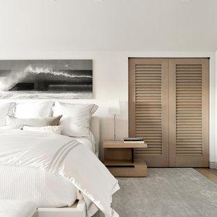 Coastal dark wood floor bedroom photo in New York with white walls
