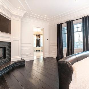 Modelo de habitación de invitados moderna, de tamaño medio, con paredes blancas, suelo de madera oscura, chimenea de esquina y marco de chimenea de ladrillo