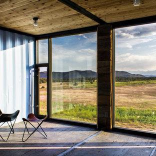 Esempio di una piccola camera degli ospiti industriale con pareti blu, pavimento in compensato e nessun camino