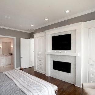 Imagen de dormitorio principal, tradicional, con paredes grises, suelo de madera oscura, chimenea lineal, marco de chimenea de baldosas y/o azulejos y suelo marrón
