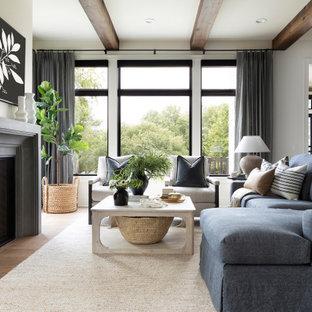 Inspiration för klassiska sovrum, med vita väggar, mellanmörkt trägolv, en standard öppen spis och brunt golv